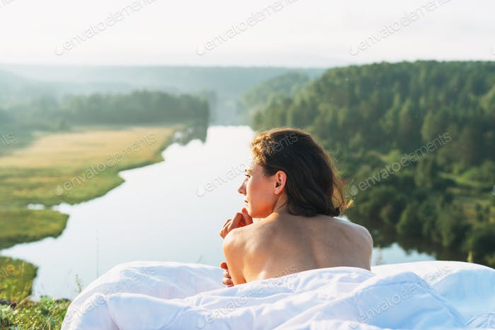 Young woman lying in the bed with white bed linen in nature against beautiful landscape