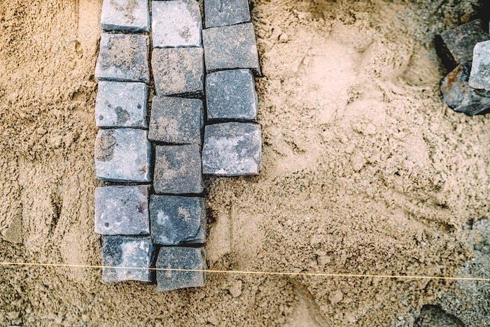Granite stones on sand path. Cobblestone blocks placement on sidewalk