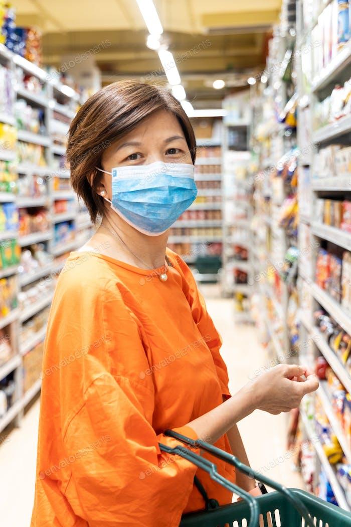 Asiatische Frauen mit Gesichtsmaske zum Schutz vor Influenza-Virus Einkaufen