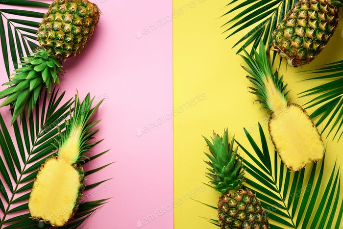 Pineapples, palm leaves on pastel colorful pink and yellow background with copy space. Creative