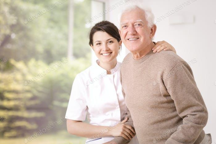 Friendly smiling caregiver hugging happy elderly man in the hosp