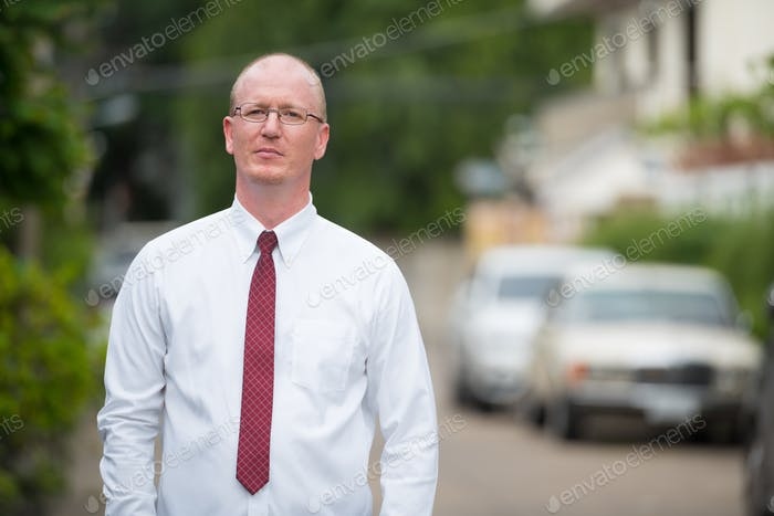 Portrait of mature bald businessman thinking outdoors