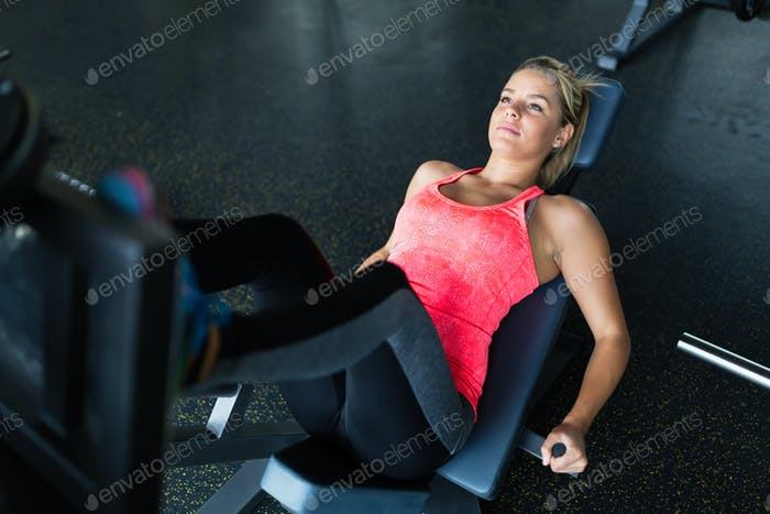 Woman doing exercises in gym for legs