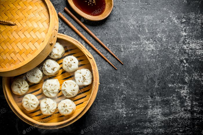 Fragrant manta dumplings in a bamboo steamer with soy sauce in a plate.
