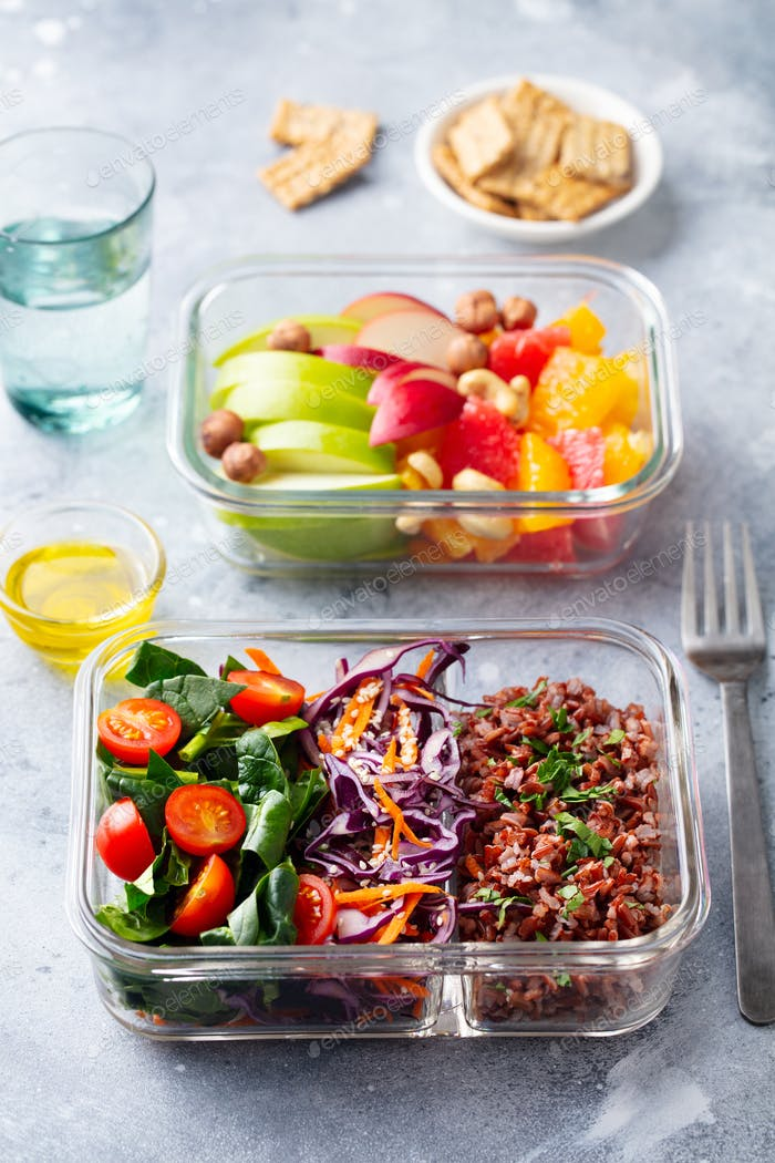 Lunch box with vegetables, brown rice and fruits salad. Healthy eating. Grey background.