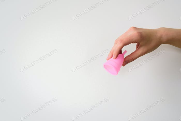 Pink menstrual cup in hand