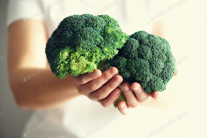 Frau in weißem T-Shirt hält Brokkoli in den Händen. Kopierraum. Gesundes sauberes Entgiftungskonzept