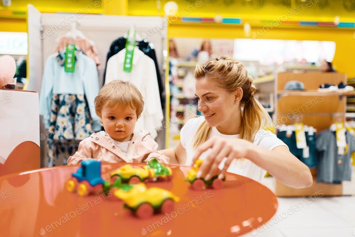 Mother with her little girl playing in kids store