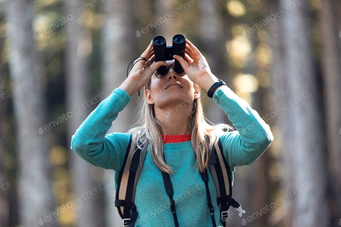 Hiker young woman looking birds through binoculars telescope in forest.