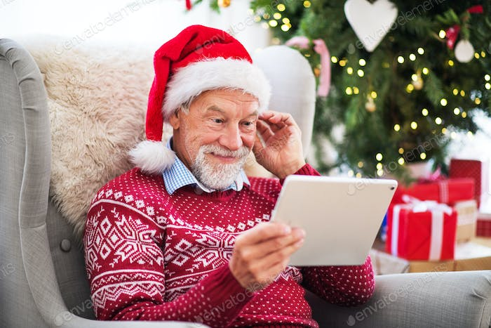 A portrait of senior man with tablet sitting on armchair at home at Christmas time.