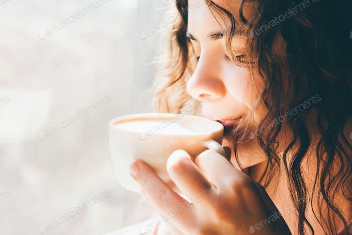 Beautiful woman drinking coffee. Close up portrait.
