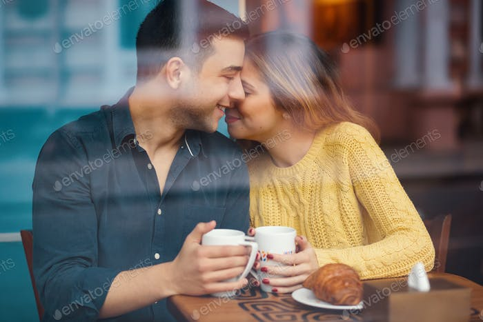Couple on date in coffee shop having a carefree conversation