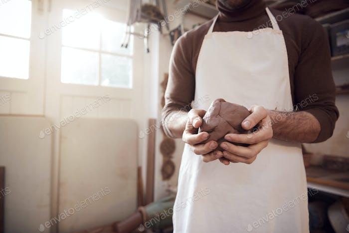 De cerca de macho alfarero llevando delantal sosteniendo bulto de arcilla en cerámica estudio