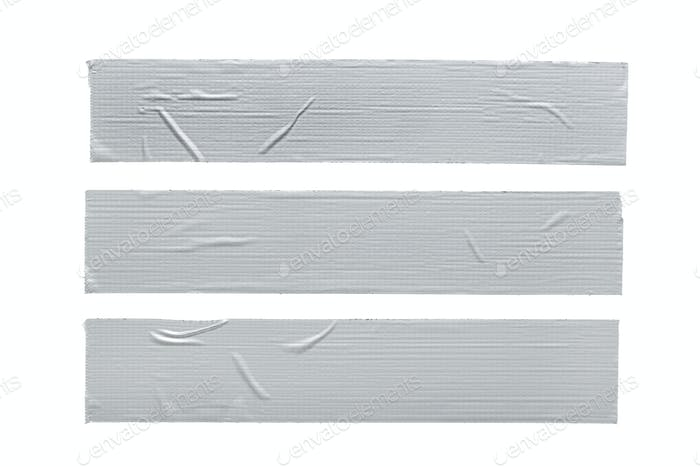 Set of three Silver grey repair duct tape pieces isolated on white background