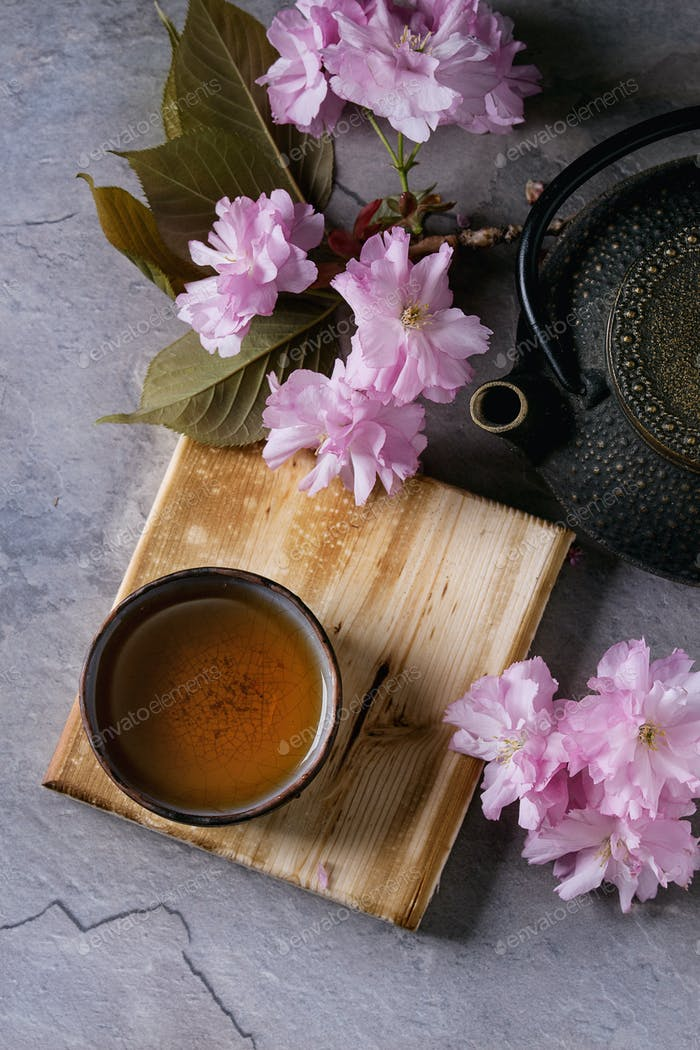 Teapot and cup of tea with blossom branch