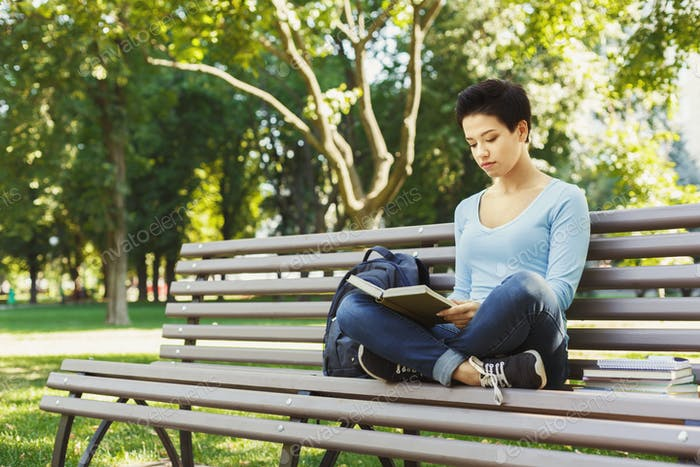 Young woman reading book in university campus