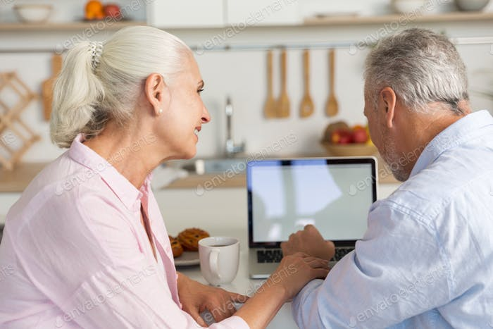Happy mature loving couple family at the kitchen using laptop