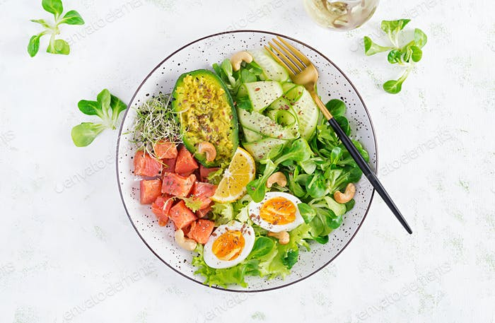 Ketogenic diet breakfast. Salt salmon salad with greens, cucumbers, eggs and avocado.