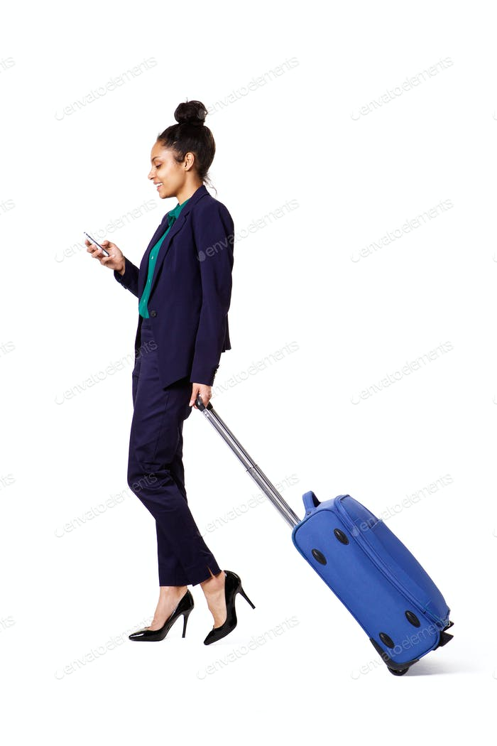 Traveling businesswoman walking with bag and mobile phone