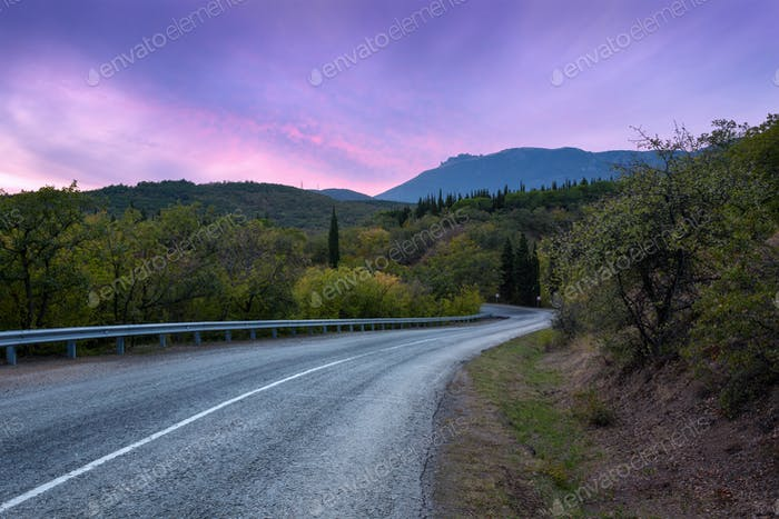 Route de montagne à travers la forêt au coucher de soleil coloré. Retour en voyage