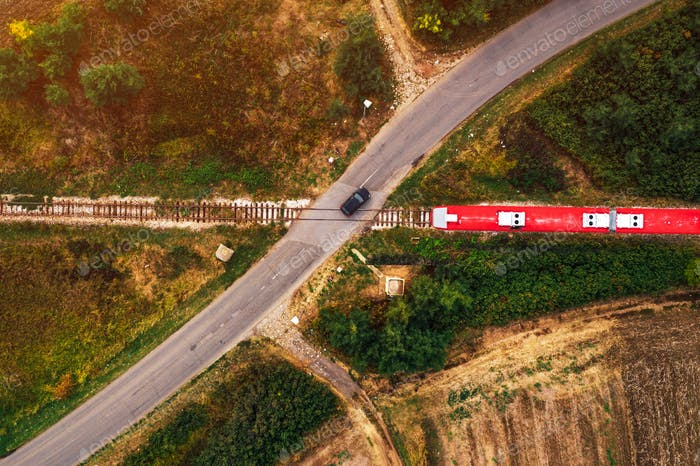 Aerial view of car and train on road junction