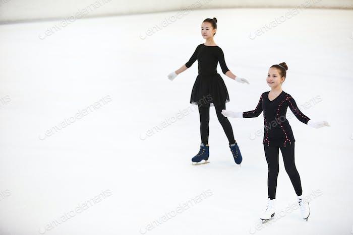 Two Girls Posing on Skating Rink
