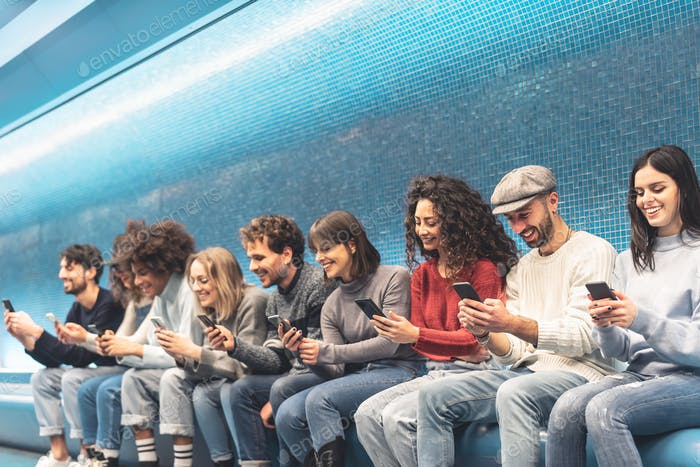 Happy friends using mobile smartphone in underground station