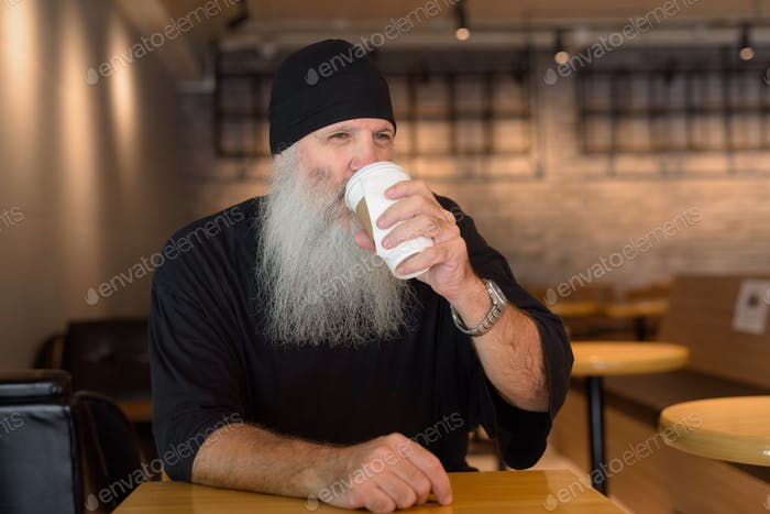 Mature handsome bearded hipster man drinking coffee at the coffee shop