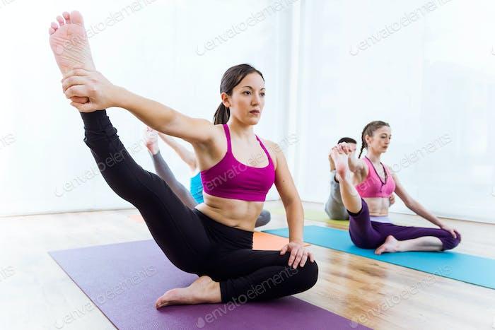 Grupo de personas practicando yoga en casa.