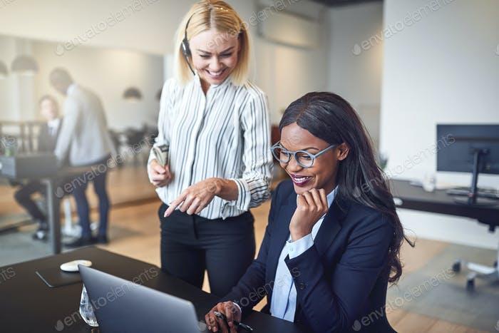 Laughing businesswomen looking at something on a laptop at work