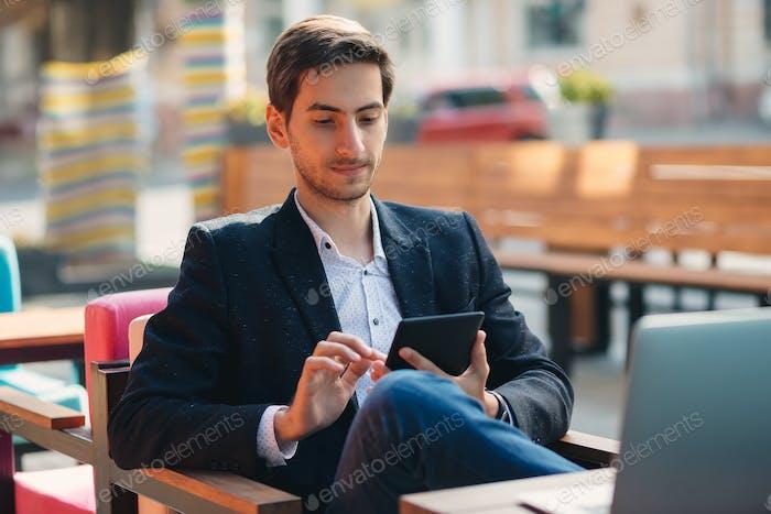 Junger Mann berührt Tablet-Bildschirm mit Finger
