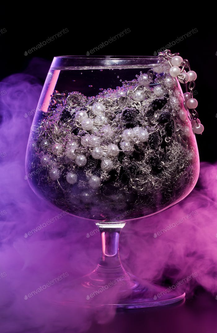 Glass with jewelry in smoke