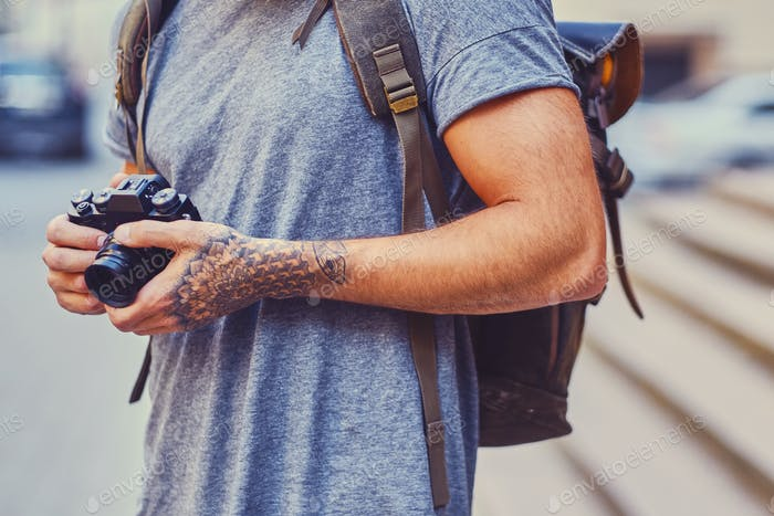 A man holds a compact film camera with tattooed arms.