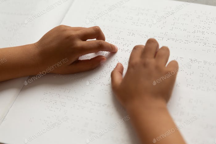 Blind schoolboy hands reading a braille book in classroom at elementary school