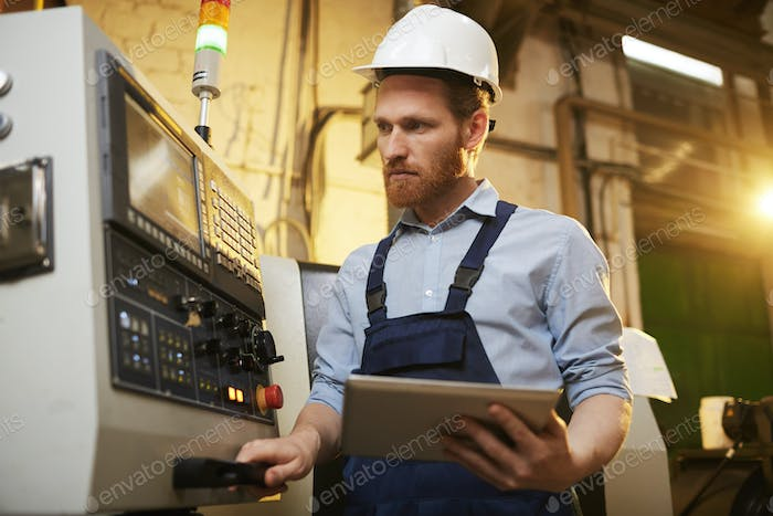 Engineer controlling the machine with tablet pc
