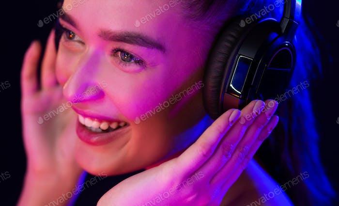 Glückliche Frau mit Headset von Neonlichtern beleuchtet