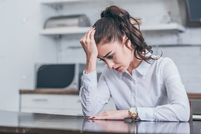 upset woman in white blouse sitting at table and crying in kitchen, grieving disorder concept