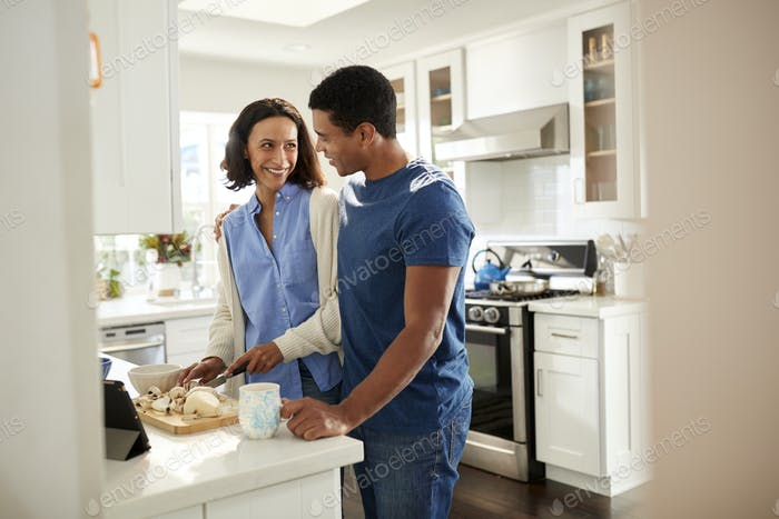 Millennial mixed race couple  standing at worktop in the kitchen preparing food