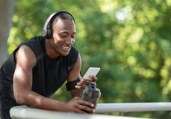 Cheerful black sporty guy chatting on phone, drinking protein