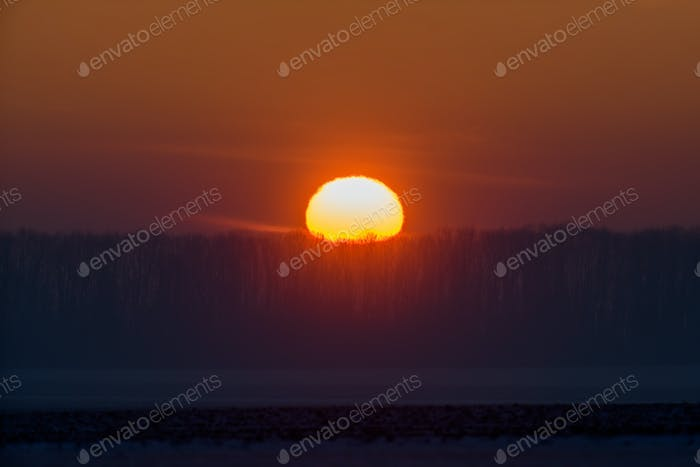 Rural landscape scene of sunrise or sunset over a farm field