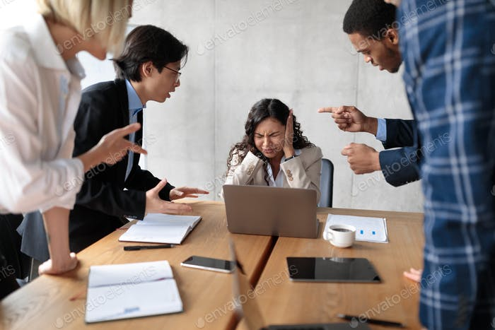 Victimized Businesswoman Covering Ears Not Listening To Aggressive Colleagues Indoor