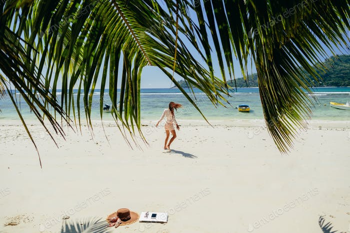 Female blogger travel and work on laptop on beach in tropics