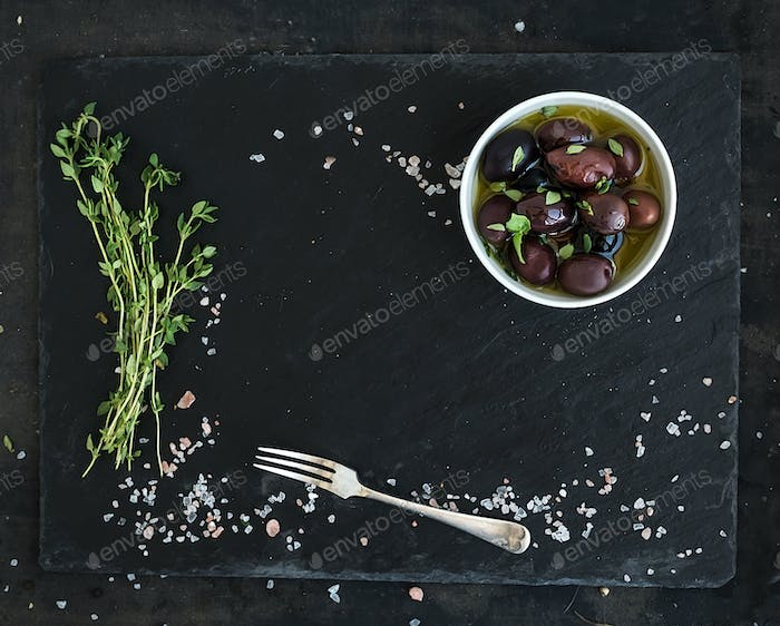 Food frame on dark stone backdrop. Mediterranean olives in oil, fresh thyme, spices
