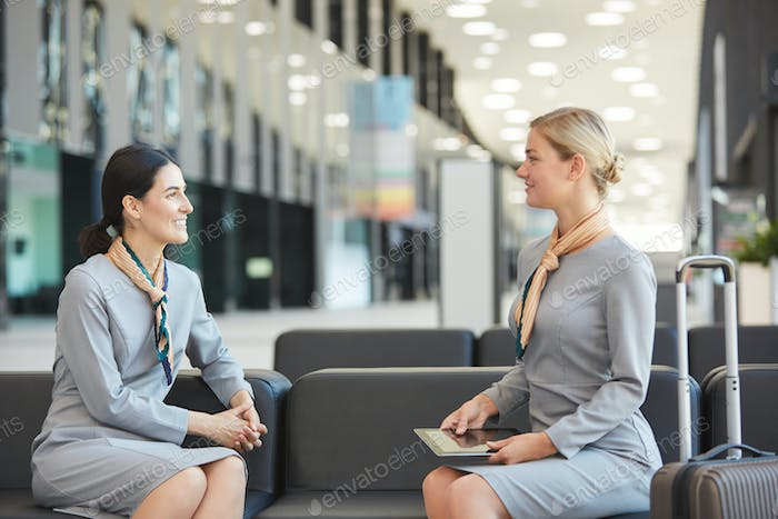 Two Flight Attendants Chatting in Waiting Lounge