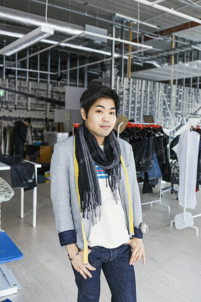 Portrait of confident male fashion designer standing in factory