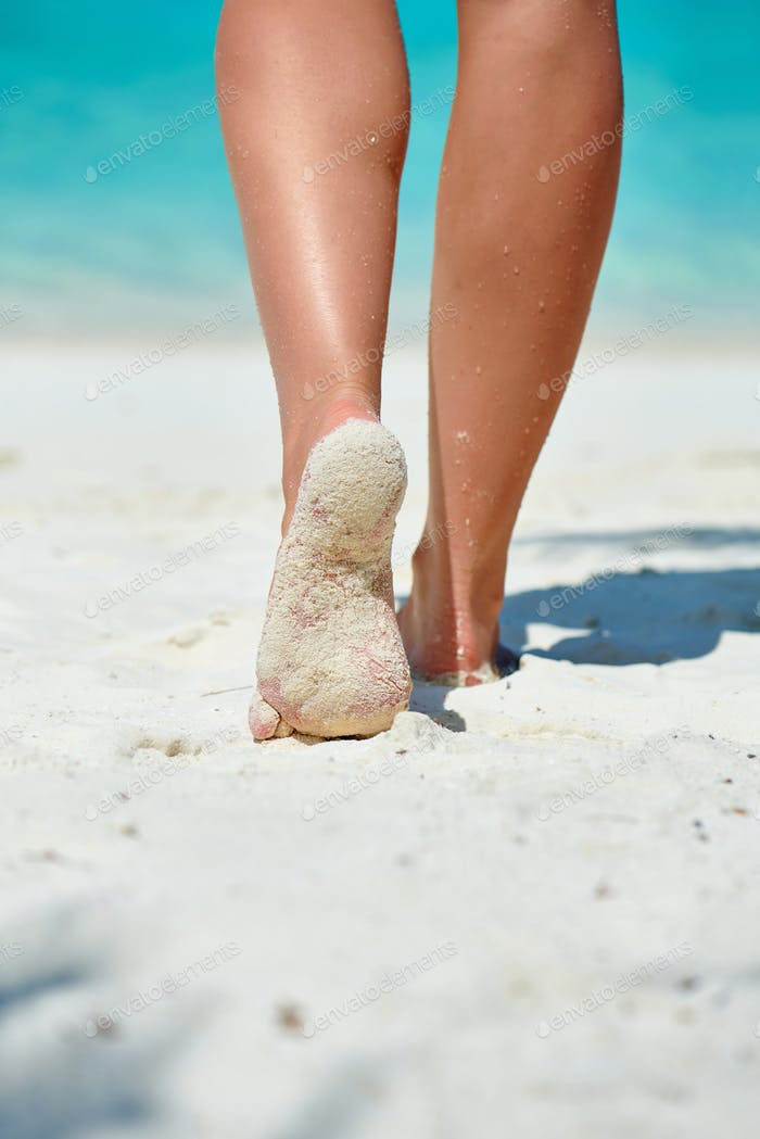 Woman walking on tropical white sand beach