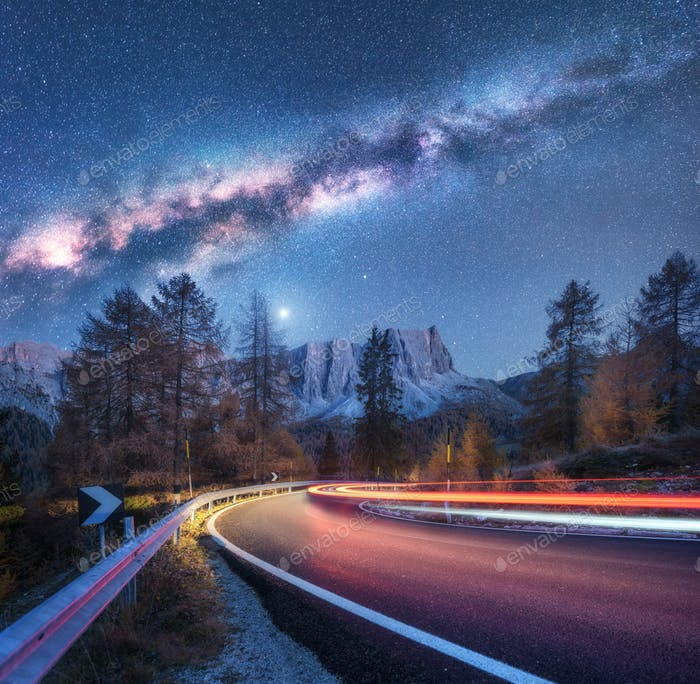 Milky Way over mountain road. Blurred car headlights