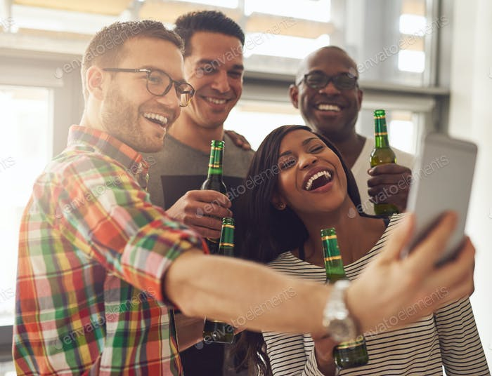 Office-Team nimmt Selfie mit Bierflaschen