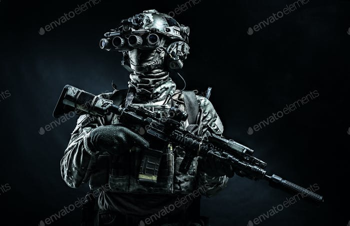 Modern combatant wearing night vision device black background