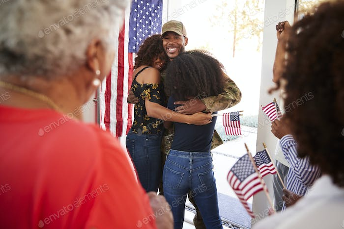 Millennial black soldier embracing his family after returning home,close up, over shoulder view